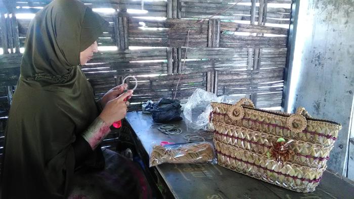 Mailiyah saat membuat kerajian,dari sampah yang di daur ulang (gus)