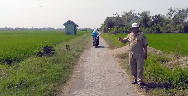 H.M.Mustoin Kasi Keuangan menunjukkan lokasi jalan berjarak 1 kilometer yang belum tersentuh bantuan PJU (gus HP)
