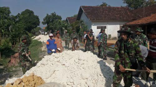 personil TNI di bantu dengan masyarakat setempat saat pembuatan jalan rabat beton poros di Desa Kelorarum, Kecamatan Tikung, Kabupaten Lamongan.
