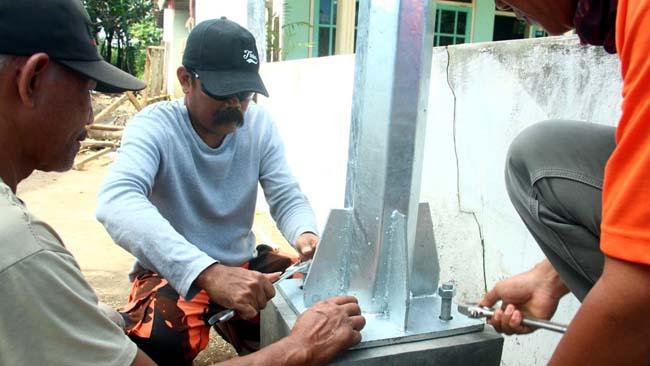MENGABDI: Proses pemasangan PJU sebagai bentuk pengabdian Sukirno. Ia tak segan untuk turun langsung memasang PJU