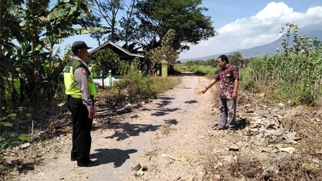 Sekretaris Desa Tanjekwagir, (kanan) Agung Siswanto didampingi Bhabinkamtimas Polsek Krembung Aiptu Ismail menunjukkan lokasi jalan rusak tanpa PJU (gus)