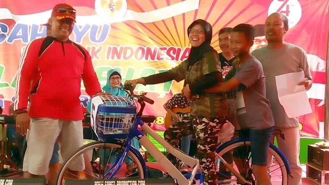 Kepala Desa Sumberejo, M. Mardjono ( kanan) dan istri menyerahkan hadia sepeda kepada pemenang undian